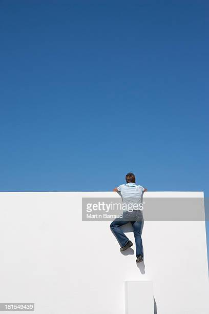 Man climbing on wall outdoors with blue sky
