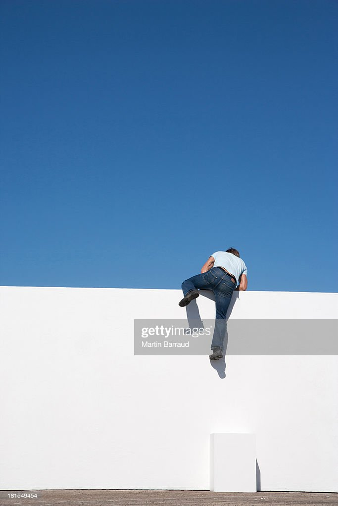 Man climbing on wall outdoors with blue sky : Stock Photo