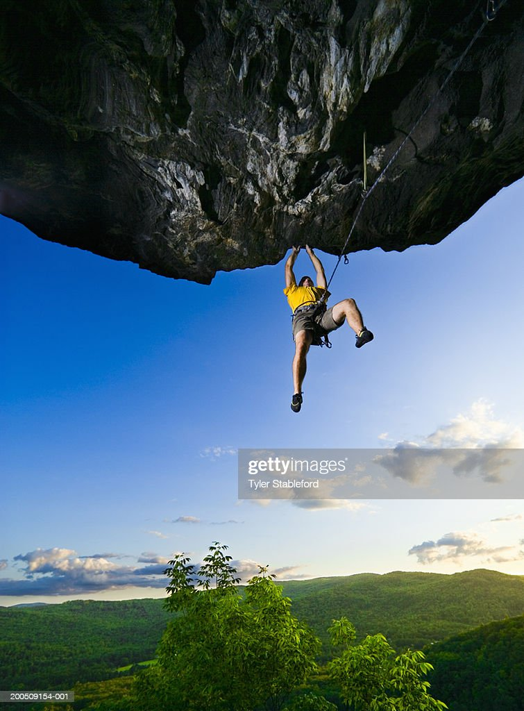 Man climbing overhanging rock, low angle view : Stock Photo