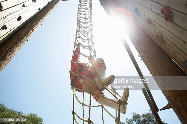 Man climbing rope ladder, low angle view