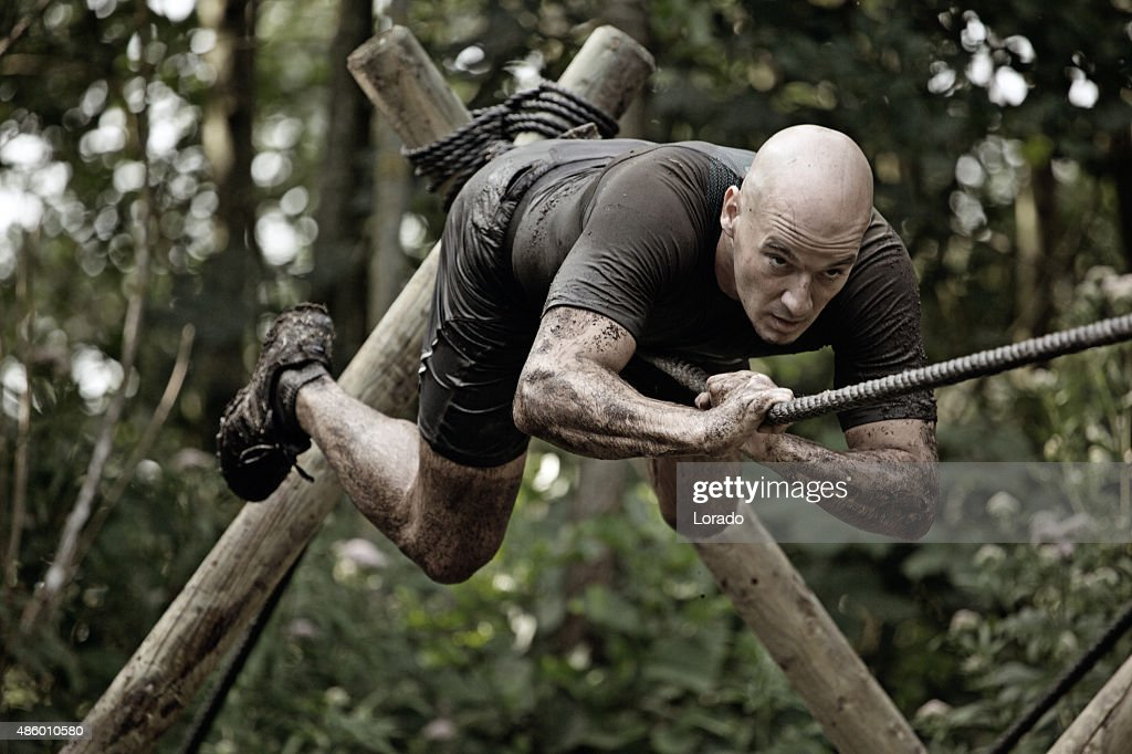 man climbing rope over mud obstacle
