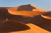 Man Climbing Sand Dunes, Namib Desert, Namibia
