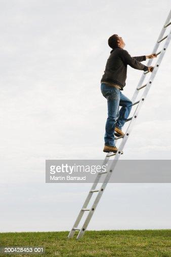 Man climbing slanted ladder on grass, side view (digital enhancement) : Stock Photo
