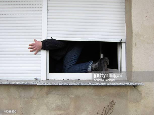 A man climbing through a window