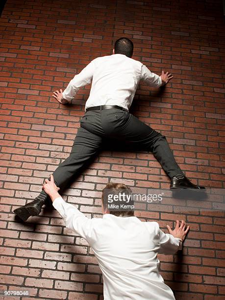 man climbing up a brick wall while another man grabs on to his leg