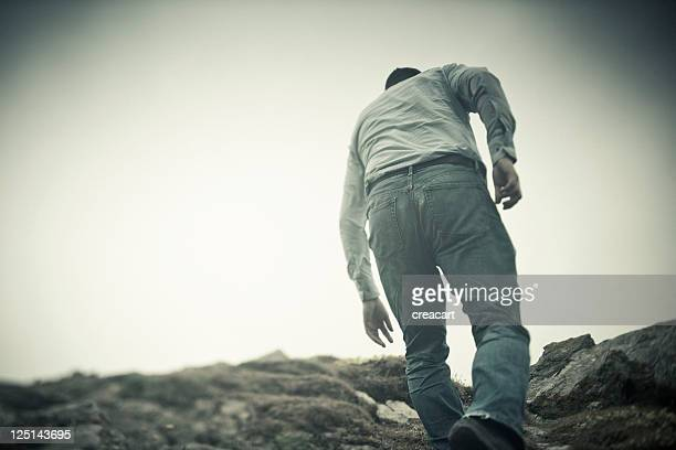 Mann Klettern auf einer stürmischen Landschaft
