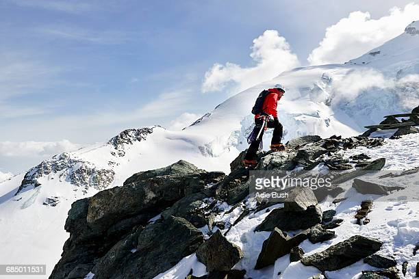 Man climbing up snow covered mountain, Saas Fee, Switzerland