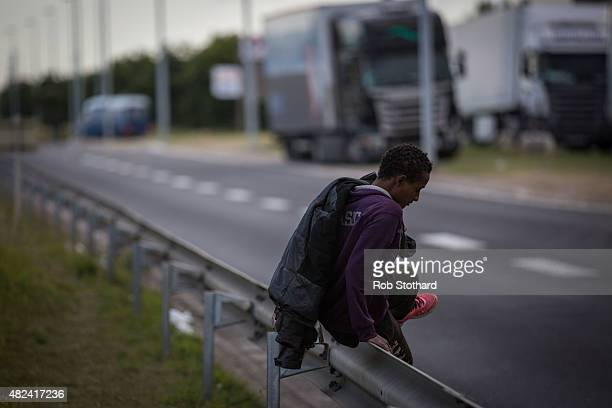 A man climbs a barrier on the side of a road leading to the Eurotunnel terminal in Coquelles on July 30 2015 in Calais France Hundreds of migrants...