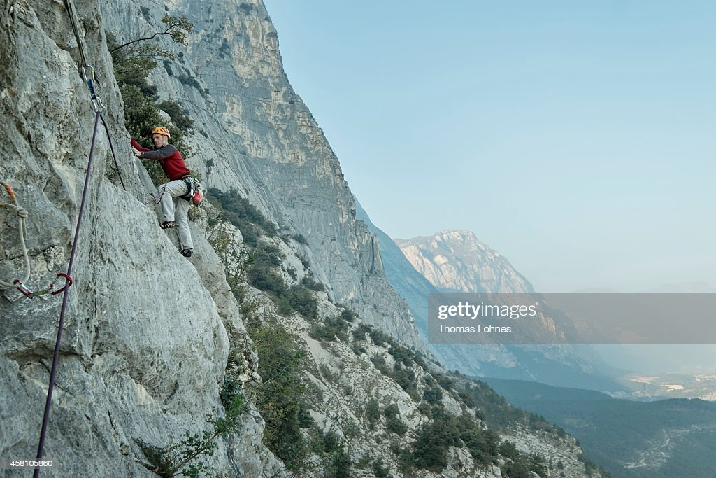 A man climbs a multipitch route on October 29 2014 in Dro near Arco Italy The mountains around Arco are a Mecca for rock climbers from single pitch...