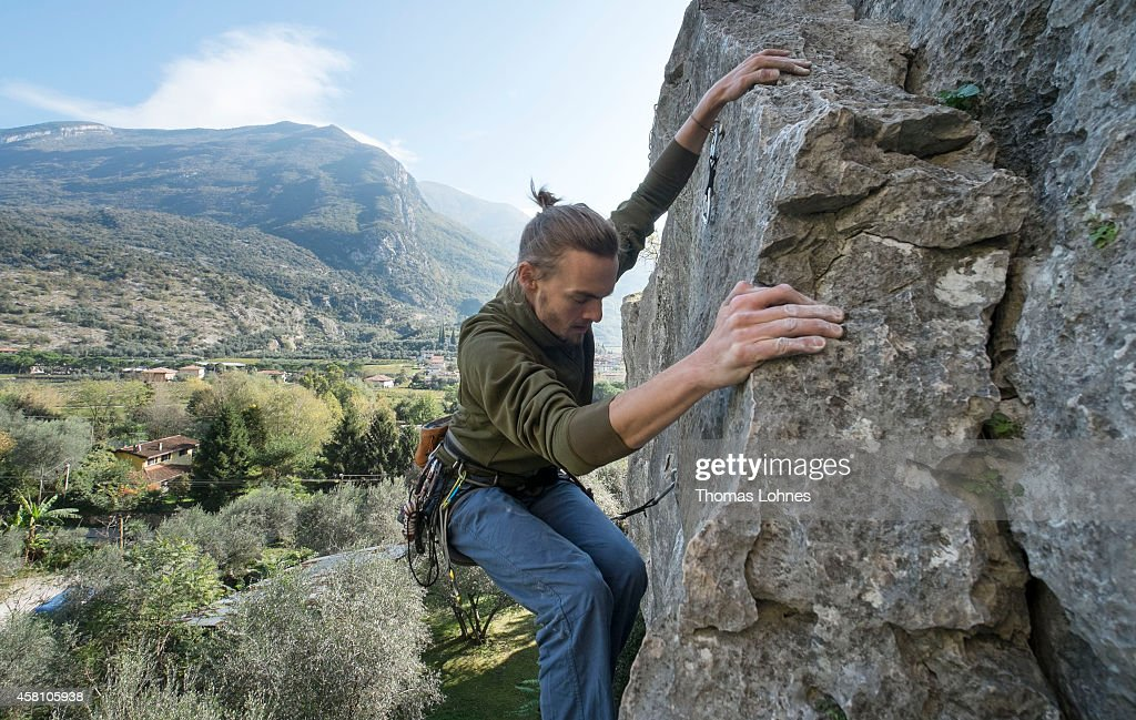 A man climbs a rock on October 27 2014 in Arco Italy The mountains around Arco are a Mecca for rock climbers from single pitch sports routes to long...