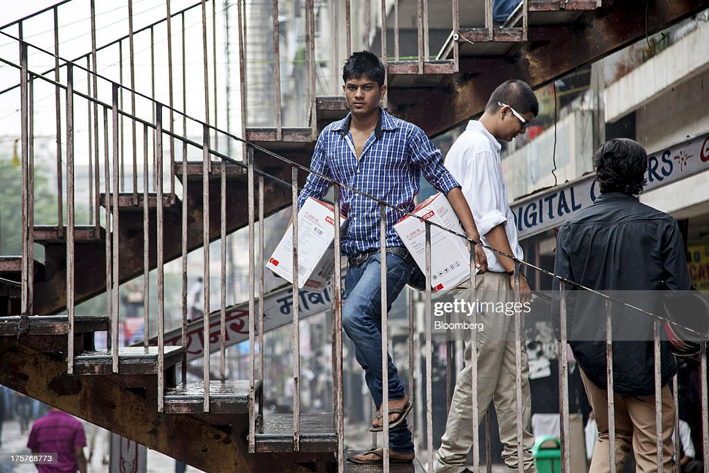A man climbs a set of stairs carrying a pair of boxed Intex Technologies India Ltd. speakers in Nehru Place IT Market, a hub for the sale of electronic goods and computer accessories, in downtown New Delhi, India, on Wednesday, Aug. 7, 2013. India's consumer price index (CPI) figures for July are scheduled to be released on August 12. Photographer: Graham Crouch/Bloomberg via Getty Images