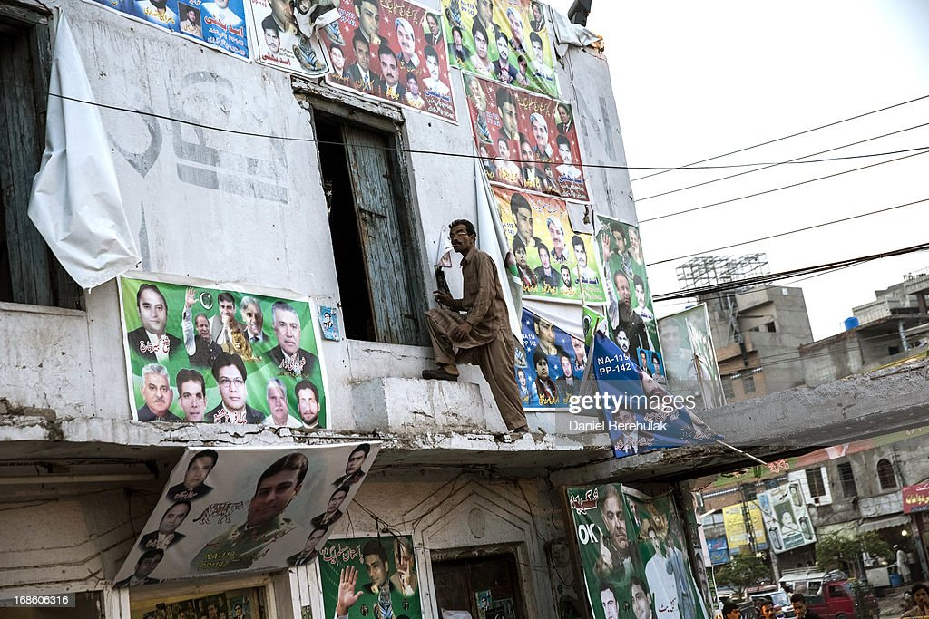 A man climbs into a doorway plastered wth PML-N party election campaign posters the day after election day on May 12, 2013 in the Old City of Lahore, Pakistan. The electoral committee recorded a high voter turn out as millions of Pakistanis cast their votes in yesterdays parliamentary elections. It is the first time in the country's history that an elected government will hand over power to another elected government. Initial results show the PML-N party has recorded the highest number of seats won and party leader.Nawaz Sharif has claimed victory ahead of the last official results.