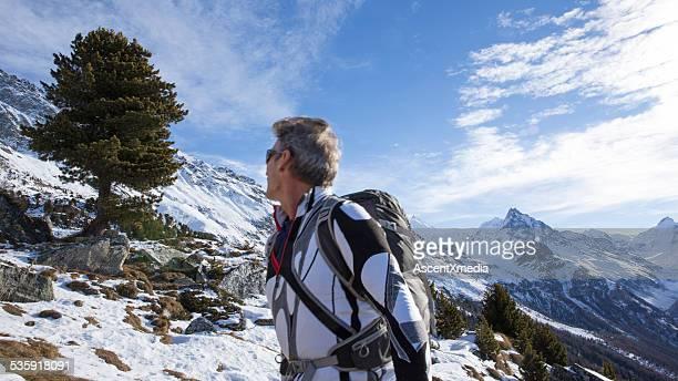 Man climbs mountain slope, looks towards solitary tree