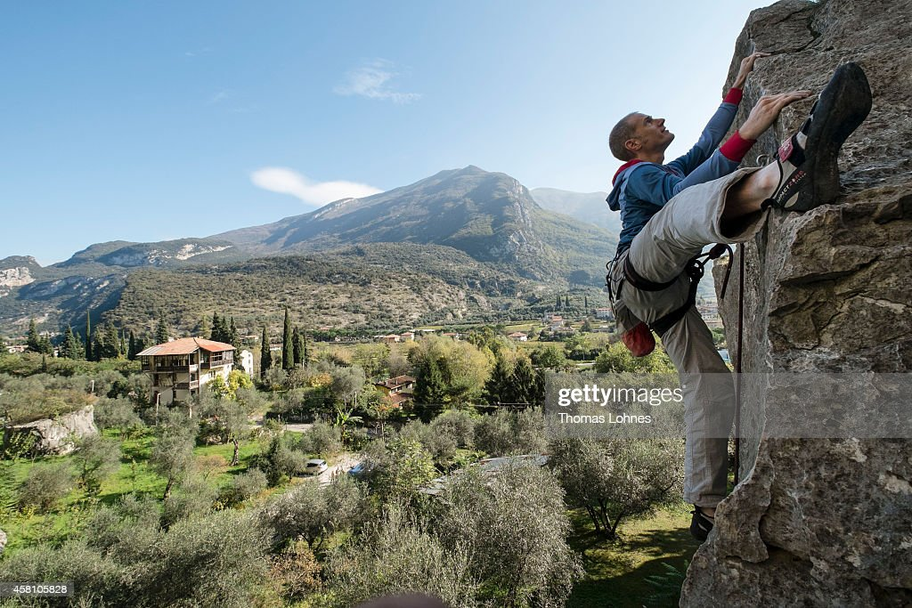 A man climbs on October 27 2014 in Arco Italy The mountains around Arco are a Mecca for rock climbers from single pitch sports routes to long...