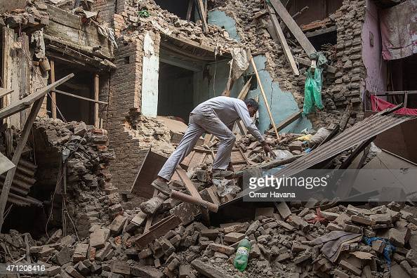A man climbs on top of debris after buildings collapsed on April 26 2015 in Bhaktapur Nepal A major 78 earthquake hit Kathmandu midday on Saturday...