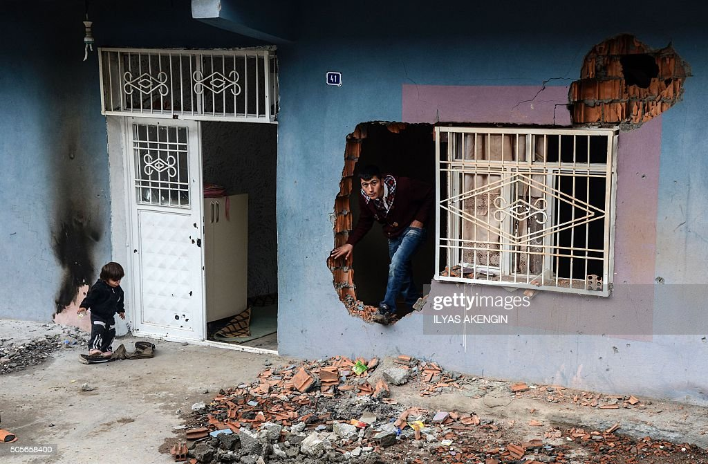 TOPSHOT A man climbs out of a hole in the wall of a house damaged during fighting between government troops and separatist Kurdistan Workers' Party...