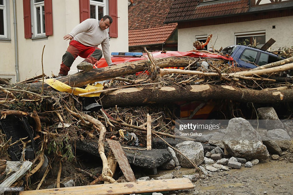 A man climbs over smashed trees, cars and other debris that cover a street in the village center following a furious flash flood the night before on May 30, 2016 in Braunsbach, Germany. The flood tore through Braunsbach, crushing cars, ripping corners of houses and flooding homes during a storm that hit southwestern Germany. Miraculously no one in Braunsbach was killed, though three people died as a result of the storm in other parts of the country.