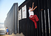 A man climbs the fence that divides Mexico and the US in Tijuana Baja California State Mexico on September 17 2014 AFP PHOTO/RONALDO SCHEMIDT