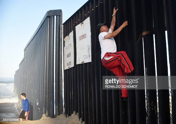 A man climbs the fence that divides Mexico and the US in Tijuana Baja California State Mexico on September 17 2014 AFP PHOTO/RONALDO SCHEMIDT / AFP /...