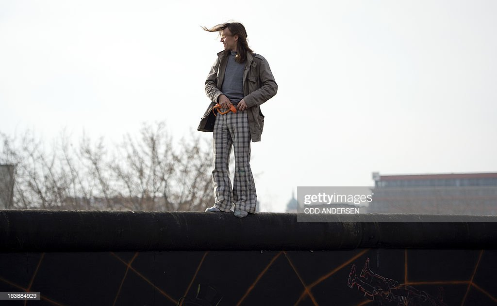 A man climbs the Wall to watch US actor and singer David Hasselhoff (unseen) touring the East Side Gallery part of the remains of the former Wall in Berlin on March 17, 2013. The former Bay Watch star was in the German capital to lend his support to the movement for that wants to preserve the 1,3km long stretch of the cold war symbol and keep the land along river Spree as public land. AFP PHOTO / ODD ANDERSEN