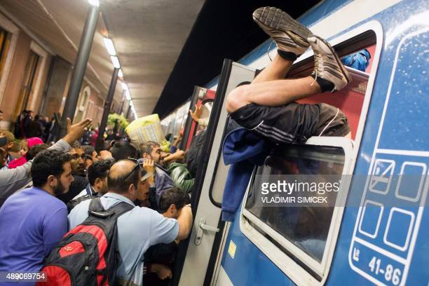 A man climbs through the window as refugees struggle to get on a train from Gyor to Hegyeshalom in Hungary on September 19 2015 During the night they...