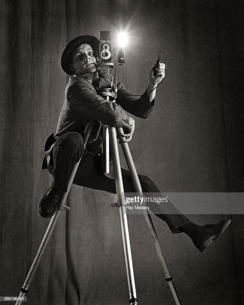 Man clinging on to camera tripod, taking photograph (B&W) : Stock Photo