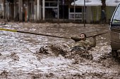 A man clings to a security line to cross a street flooded by the overflowing of the Copiapo River due to heavy rainfall that affected some areas in...