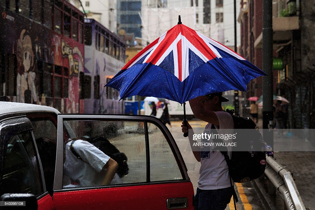A man closes his umbrella designed like the British flag as he enters a taxi with his companion during a downpour in Hong Kong on June 28, 2016. Hong Kong stocks ended slightly lower on June 28, unable to match an Asian rebound from last week's Brexit-fuelled selloff because of its exposure to Europe-linked companies. / AFP / ANTHONY
