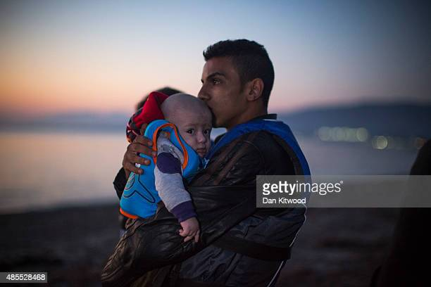 A man clutches his child as migrant families from Syria arrive in an inflatable dinghy on the beach at sunrise on the island of Kos after crossing a...