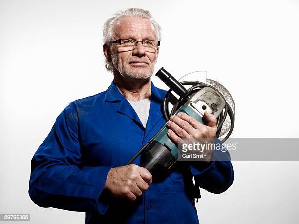 A man clutching a circular saw