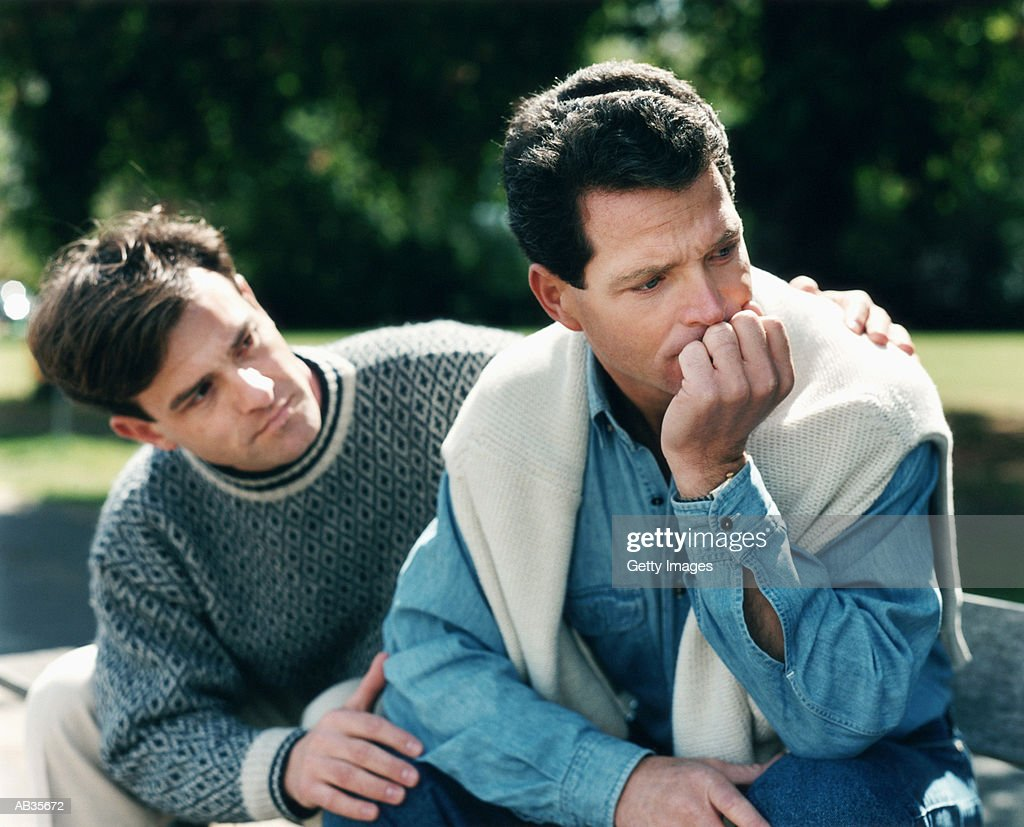 Man coforting male friend on park bench : Stock Photo