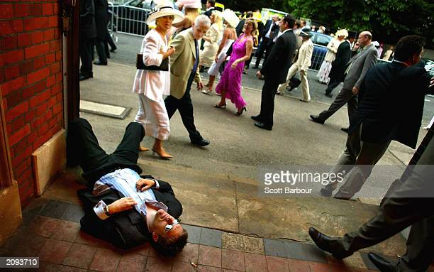 A man collapses on the ground drunk as racegoers walk past June 18 2003 during the second day of the Royal Ascot horse racing week in Ascot England...