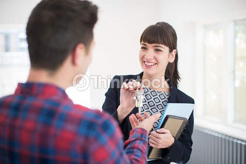 Man Collecting Keys To New Home From Female Realtor : Stock Photo