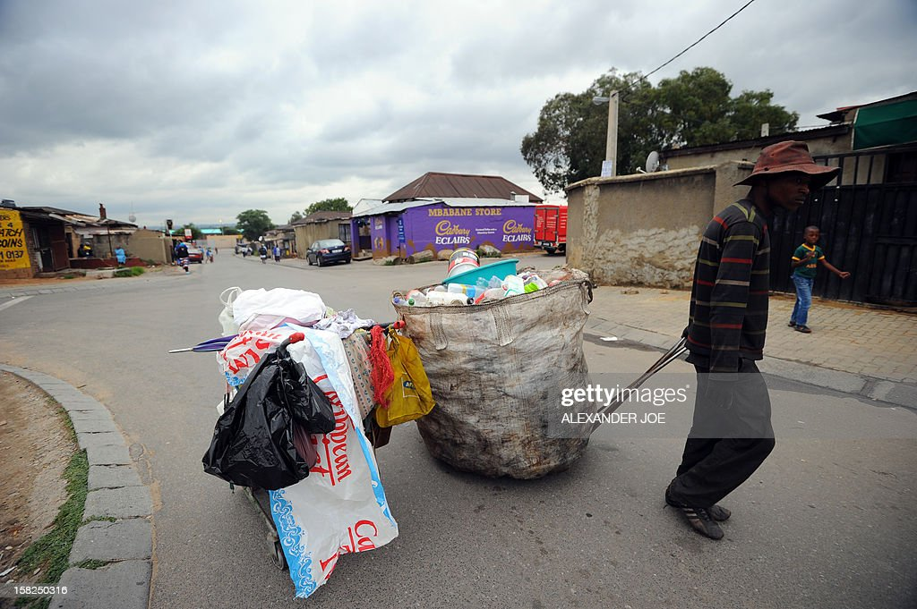 A man collecting plastic bottles carries his cart through the streets of Johannesburg's Alexandra township on December 12, 2012.