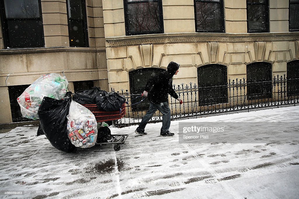 A man collects cans during a snow storm on December 14, 2013 in the Brooklyn borough of New York City. Much of the Northeast was hit by a storm stretching over 1,000 miles that could result in at least a foot of snow on parts of New England.