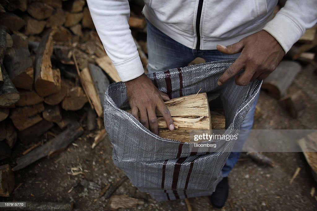 A man collects cut logs for heating from a firewood supply store in Athens, Greece, on Friday, Dec. 7, 2012. Greece, the epicenter of Europe's debt crisis since revealing a bloated spending gap in late 2009, has faced regular demands to get a firmer grip on the budget or risk being forced out of the euro. Photographer: Kostas Tsironis/Bloomberg via Getty Images