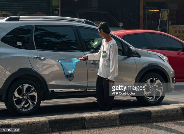 A man collects donations from motorists for a mosque in Jakarta on July 26 2017 / AFP PHOTO / BAY ISMOYO