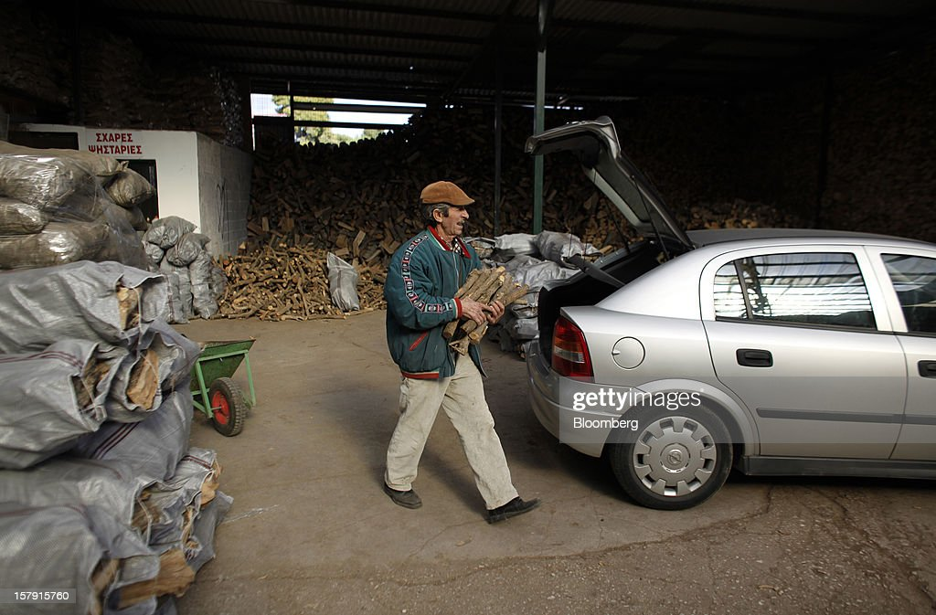 A man collects firewood from a wood supply yard in Athens, Greece, on Friday, Dec. 7, 2012. Greece, the epicenter of Europe's debt crisis since revealing a bloated spending gap in late 2009, has faced regular demands to get a firmer grip on the budget or risk being forced out of the euro. Photographer: Kostas Tsironis/Bloomberg via Getty Images