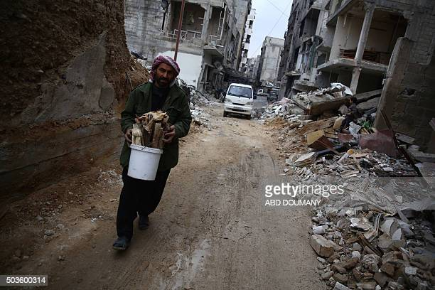 A man collects firewood from the rubble of destroyed buildings in the rebelheld town of Douma on the eastern edges of the Syrian capital Damascus on...