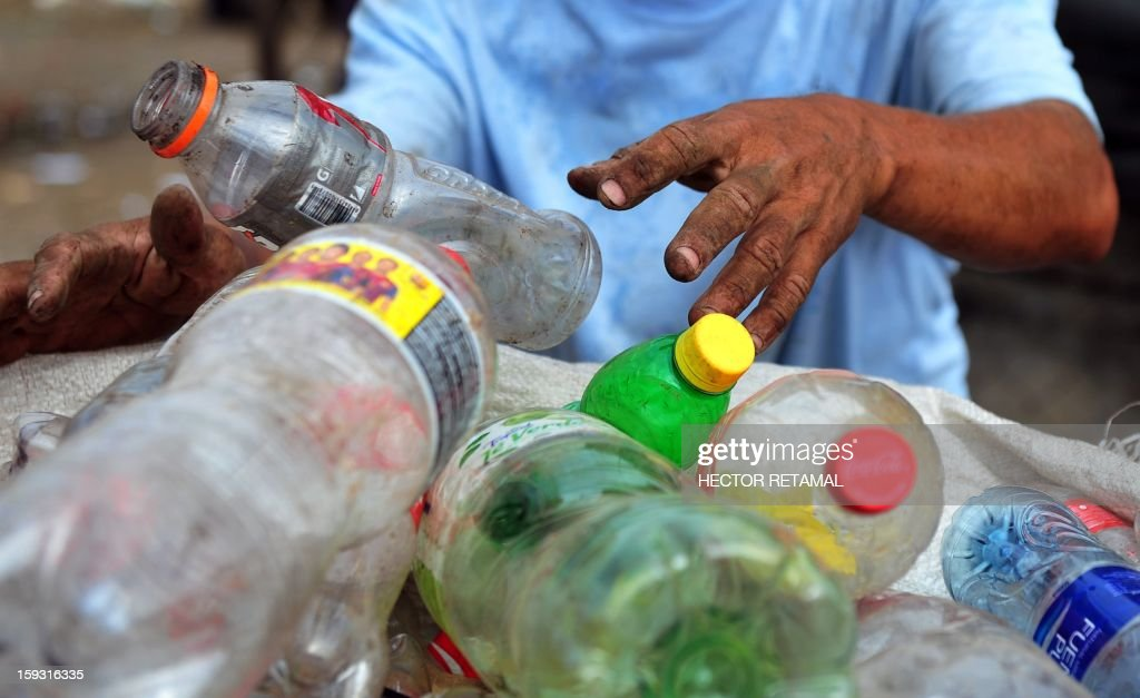 A man collects plastic bottles to sell for recycling, in a landfill of Managua, on January 11, 2013. AFP PHOTO/Hector RETAMAL