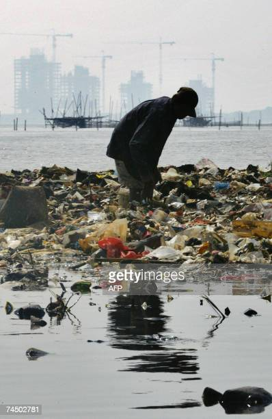 A man collects plastic waste from a polluted river near Jakarta bay 10 June 2007 Indonesia is particularly vulnerable to the impact of climate change...