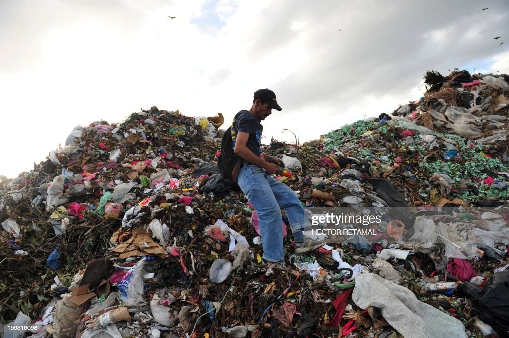 A man collects plastics and metals to be sold for recycling, at Managua's landfill 'La Chureca', on January 10, 2013. AFP PHOTO/Hector RETAMAL