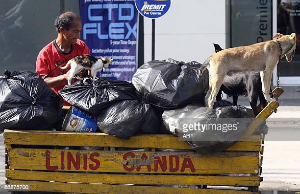 A man collects recyclable materials near a bank building in Manila on July 7 2009 Five million of the Philippines poorest families will receive cash...