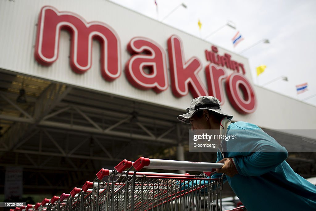 A man collects shopping carts outside a Makro store, operated by Siam Makro Pcl, in Bangkok, Thailand, on Tuesday, April 23, 2013. Billionaire Dhanin Chearavanont's CP All Pcl, Thailand's 7-Eleven chain, offered to pay about $6.6 billion for discount retailer Siam Makro Pcl in the biggest takeover announced in Asia this year. Photographer: Brent Lewin/Bloomberg via Getty Images