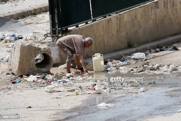 A man collects stagnant murky water from the side of a road in a rebelheld area in Aleppo on May 12 2014 Residents of Syria's second city Aleppo have...