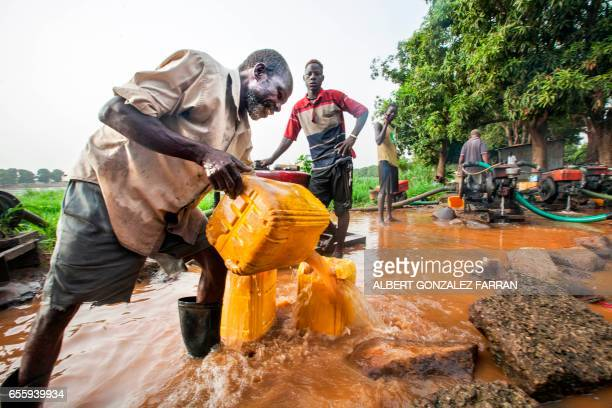 A man collects water directly pumped from the Nile river on March 21 2017in Juba South Sudan to distribute to local residents for drinking...