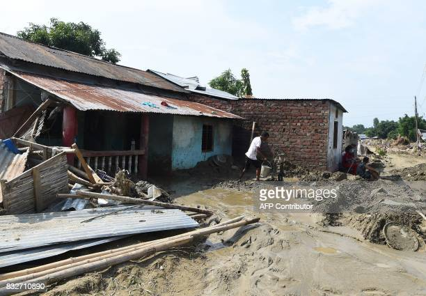 A man collects water from a pump in front of his house damaged by flood in Itahari Sunsari district some 250 kms from Nepal's capital Kathmandu on...