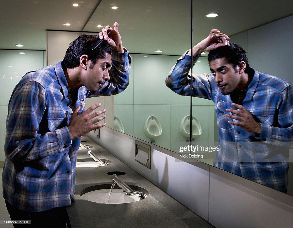 Man combing hair in bathroom mirror : Stock Photo
