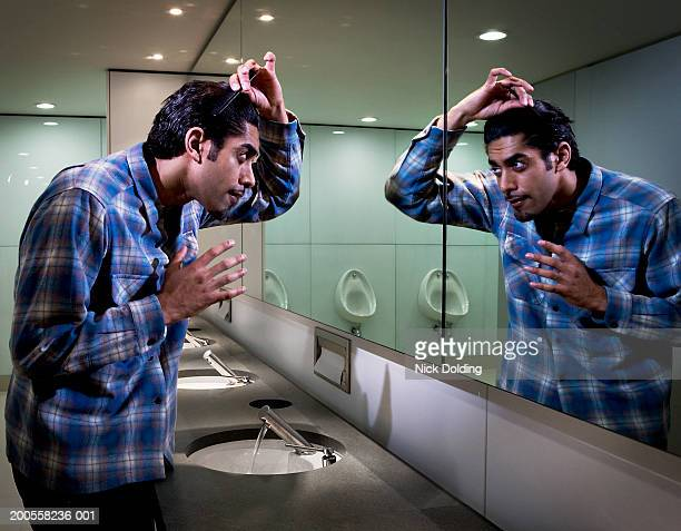 Man combing hair in bathroom mirror