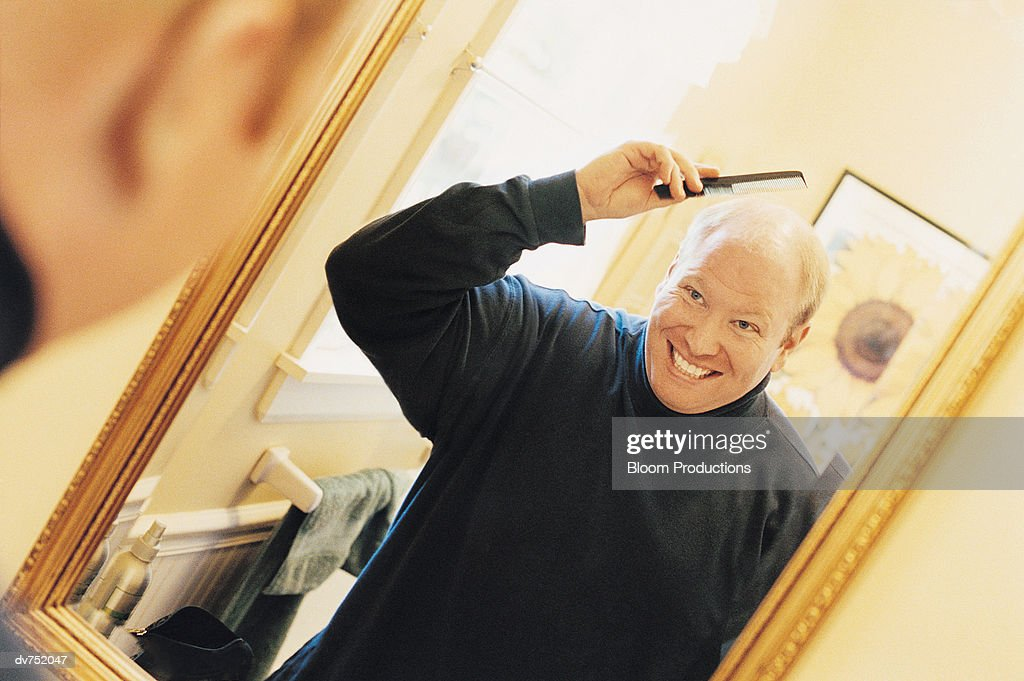 Man Combing His Hair in a Mirror : Stock Photo